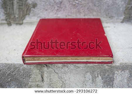 Old red book placed on concrete stairs. You can design and add text or products.