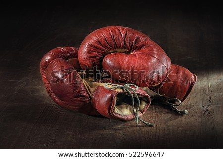 Old red boxing gloves on wooden background.