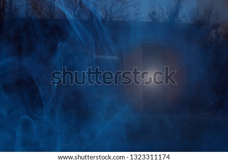 old red brick building at night around a ghostly blue fog and a doorway a mysterious glow the concept of mystery and Halloween #1323311174