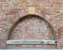 Old red brick wall with an arc and a stone bench