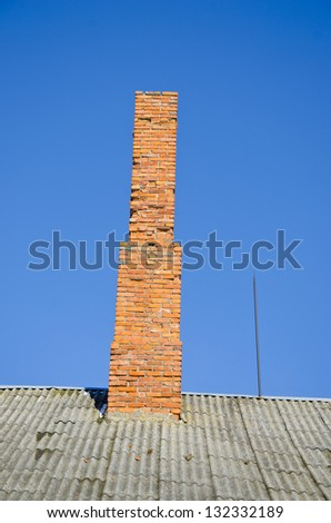 old red bricks chimney on roof and blue sky background