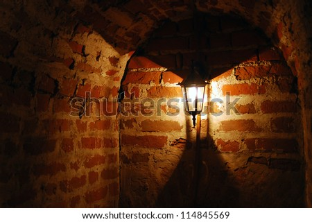 Old red bricks wall and light hanging on the wall. Kremlin in Kolomna, Moscow region, Russia.