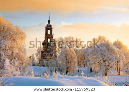 Old red church tilt with white trees on hill in Russia, winter season