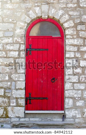 Old red door on a stone building