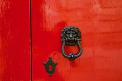 Old red door with lion head metal knockers, Mdina, Malta.