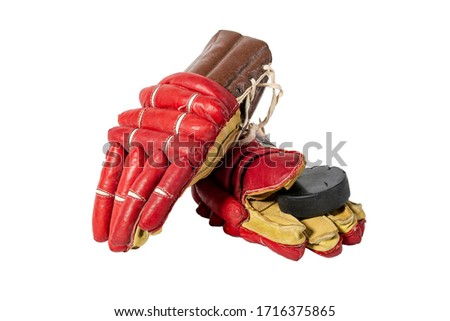 Old red hockey gloves for goalkeeper. Isolated over white background. Hockey puck. The concept of the game of hockey and hockey sport.