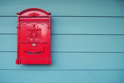 Old red mailbox on wooden walls painted blue, thailand.