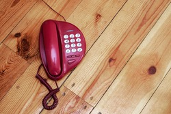 Old red retro telephone with cable and wire stands on wooden floor or table. Concept history of telephony.