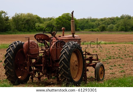 Old red rusty farm tractor at the edge of a field - stock photo