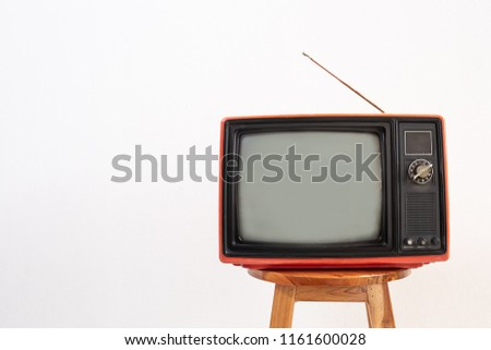 Old red television receiver on wood chair isolated on white background. Retro, vintage TV  technology style, copy space of left