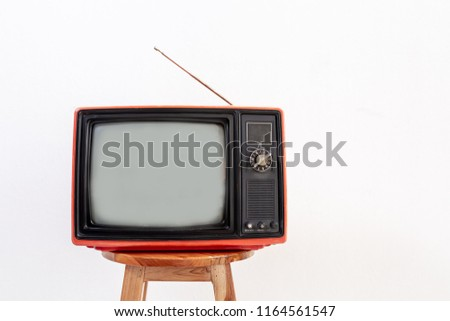 Old red television receiver on wood chair isolated on white background. Retro, vintage TV  technology style