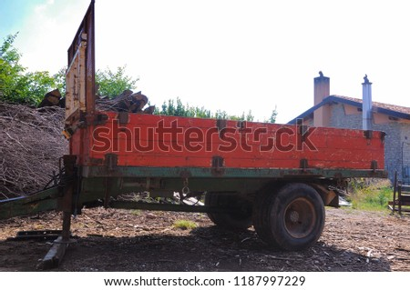 Old red trailer for transporting logs.
