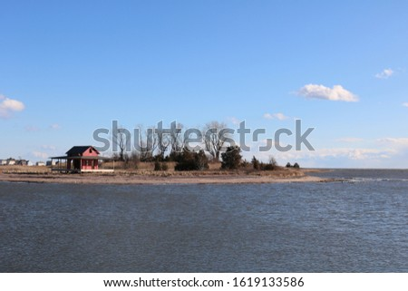 Old red weathered fishing shed shack on New England coastal bay pier shoreline beach