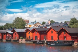 Old red wooden Finnish houses and barns are on the river coast. Porvoo old town, Finland