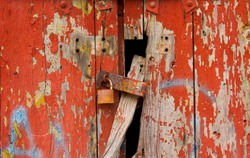 old red wooden wall peeling texture and corroded padlock