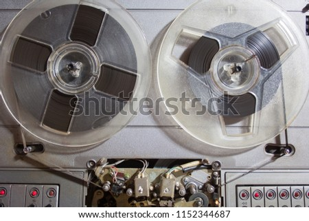Old reel-to-reel recorder with magnetic tape on it #1152344687