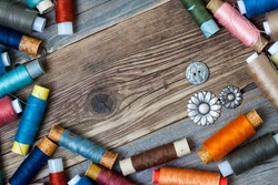 old reels of varicolored thread and vintage buttons on the textured surface of the ancient tailor's table