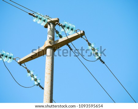 Old, reinforced concrete pylon of an overhead power line with light azure bundle conductors attached on its cables on a blue sky background #1093595654