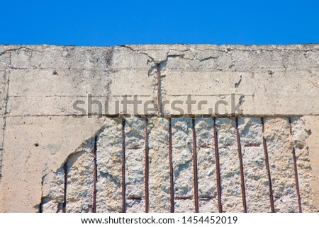 Old reinforced concrete structure with damaged and rusty metallic reinforcement that must be demolished.