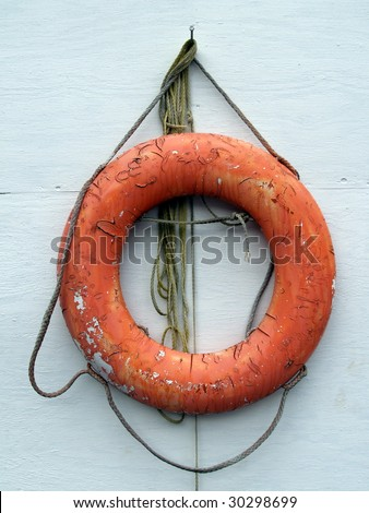 old rescue life saver ring against a boathouse
