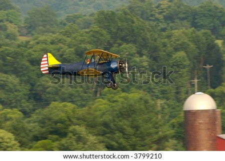 Old, restored biplane flying low and slow at air-show
