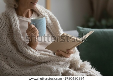 Old retired 70s lady reading book at home, drinking hot tea, resting on sofa in cozy living room. Mature reader wrapped in knitted blanket relaxing with novel over cup of coffee or chocolate. Close up Stock photo ©