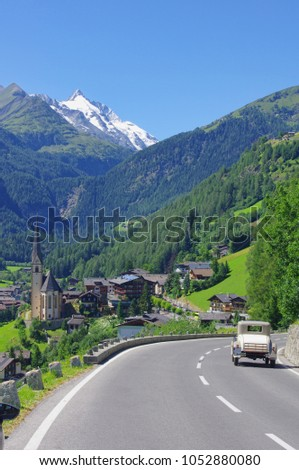old retro car driving in the Austria Alps. Heiligenblut church and Grossglockner peak in the Alps