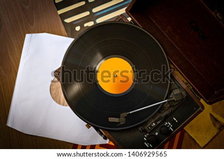 Old retro case gramophone player with vinyl plaing and vinyl covers top view Foto stock ©
