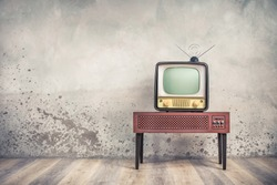 Old retro classic analog CRT TV set receiver and aged wooden television stand with outdated amplifier front aged concrete wall background. Broadcasting, news concept. Vintage style filtered photo