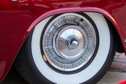 old, retro, classic wheel car tire from 1950s in havana style, crimson shining body, reflections on the rim, oldtimer