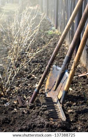 Old retro garden tools (cultivator, shovel, rake) over brown soil (ploughed land) close up, vertical.  Agriculture, gardening, soil cultivation, village life concept.