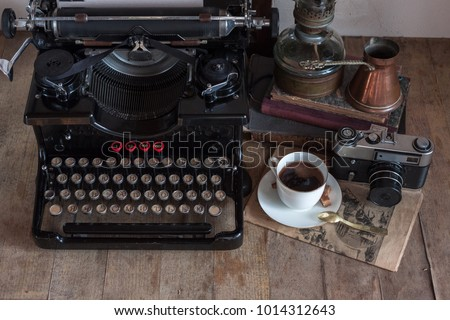 Old retro journalist typewriter with cup of coffee, copper jug, gas lamp, books, newspaper, typewritter on wooden rustic background. #1014312643