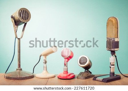 Old retro microphones for press conference or interview front mint green wall background Stockfoto ©