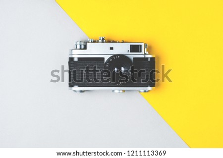 Old retro photo camera on grey-yellow background