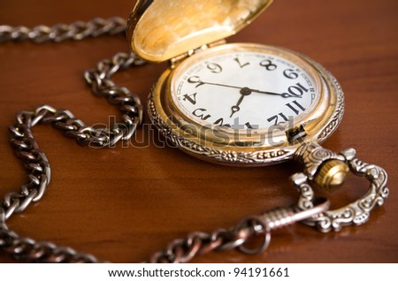 Old retro pocket watch with chain on table