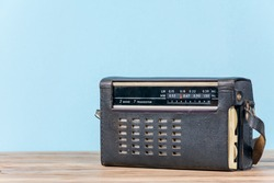Old retro radio receiver on wooden table and blue background