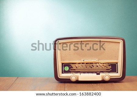 Old retro radio with green eye light on table front gradient background