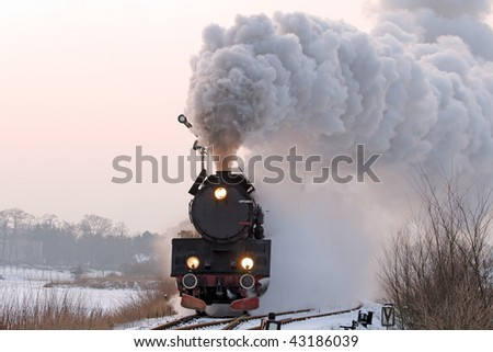 Old retro steam train starting from the station during wintertime