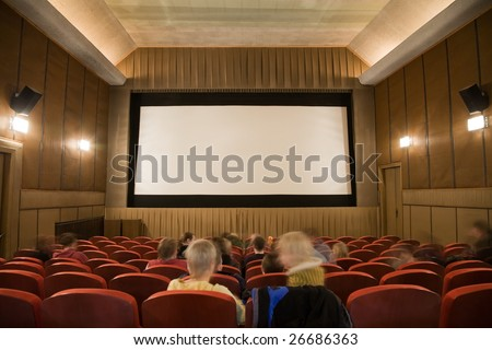 Old retro style cinema auditorium with line of red chairs, sitting visitors and silver screen. Ready for adding your own picture.