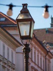 Old retro styled street lantern with electric lamp in the Ljubljana city. Metal antique streetlight for urban illumination in vintage design. Street lantern streetlight on a post closeup in Ljubljana.