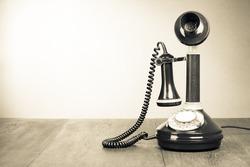 Old retro telephone on table vintage style sepia photo