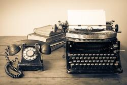 Old retro telephone, typewriter, books on table. Vintage style sepia photo