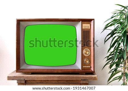 old retro TV with blank green screen for a designer, video film stands in a light room on a wooden table, ficus houseplant nearby, concept of a cozy house 1960-1970, stylish mockup Stockfoto ©