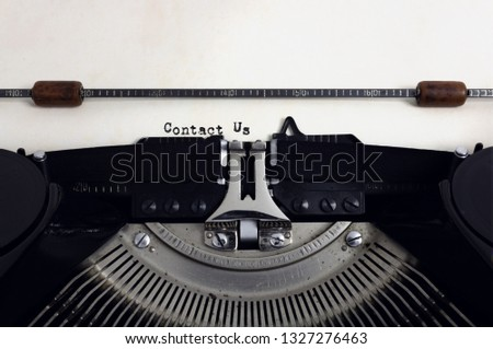 Old retro vintage black typewriter with close-up typing text Contact Us as heading on aged paper #1327276463