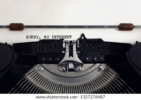 Old retro vintage black typewriter with close-up typing text Sorry No Internet as heading on aged paper