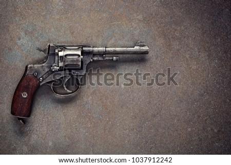 Old revolver on  vintage dark background.