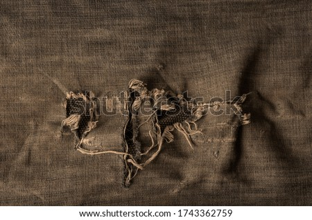 Old ripped jeans background. A detailed shot of a fragment of denim with holes. Creative background for various design tasks. Copy space. Photo stock ©