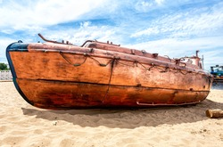 Old river motor boat on the sandy bank of the river. Broken abandoned motor boat