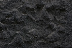 Old rock black wall. Vintage cliff texture and background. Stone dark abstract surface and pattern.