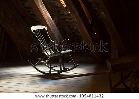 Old rocking chair on a dim attic #1054811432